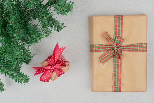 Zwei niedliche geschenkboxen mit grünem lametta auf grauer wand.