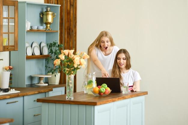 Zwei niedliche junge frauen, die online-shopping machen, waren finden und diskutieren