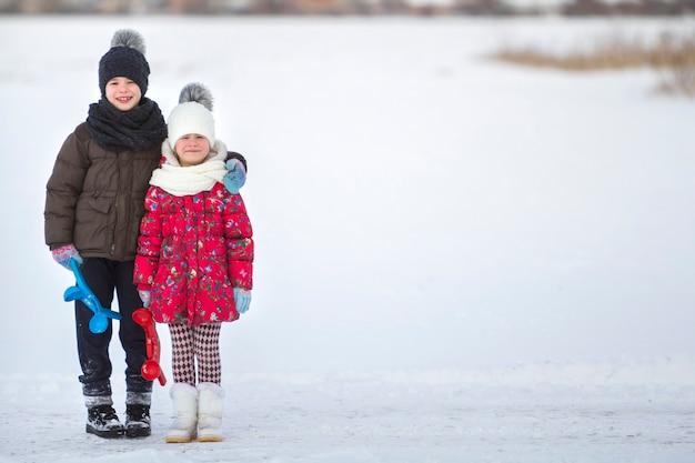 Zwei niedliche junge glückliche lächelnde kinder in warmer kleidung mit hellen neuen schneeklammern, die zusammen am kalten wintertag auf weißem hellem verschwommenem kopienraum aufwerfen. aktivitäten im freien, ferienspiele.