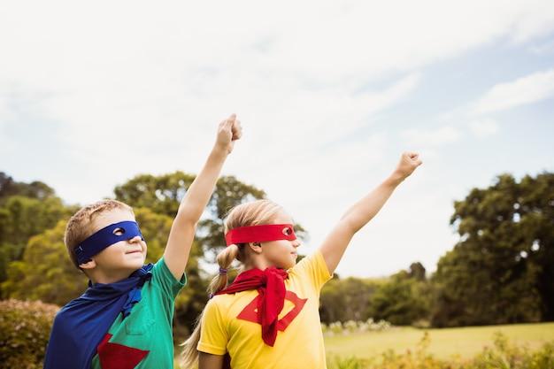 Zwei niedliche kinder, die vortäuschen, im superheldkostüm zu fliegen