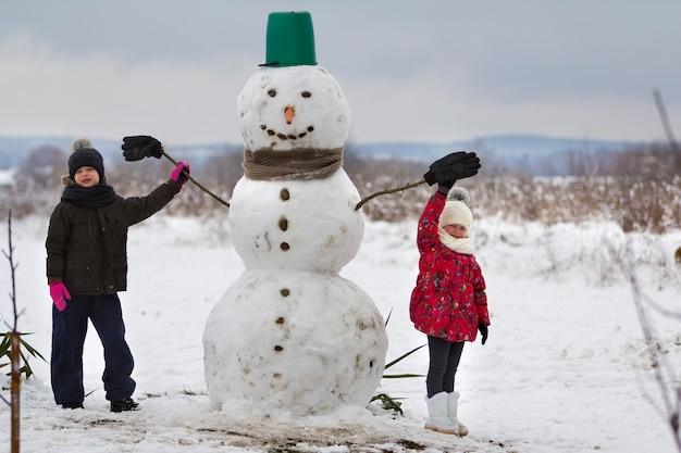 Zwei niedliche kinder, junge und mädchen, die vor lächelndem schneemann stehen