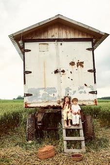 Zwei niedliche kinderjungen und -mädchen gekleidet in weißem leinentuch, das erdbeeren auf dem feld erntet und spaß nahe dem anhänger hat