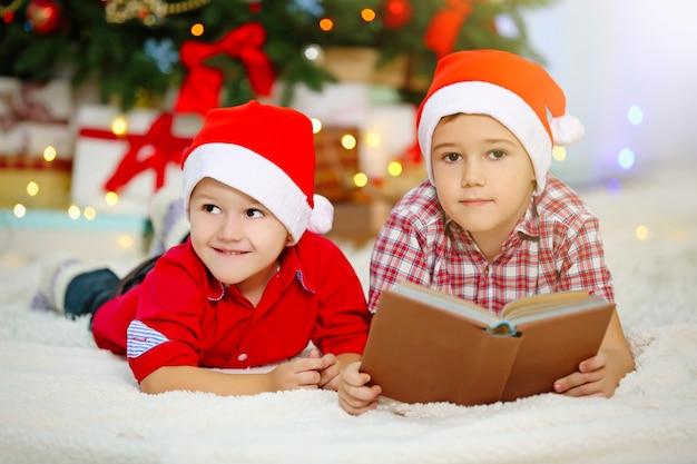 Zwei niedliche kleine brüder, die buch auf weihnachtsdekorationsoberfläche lesen