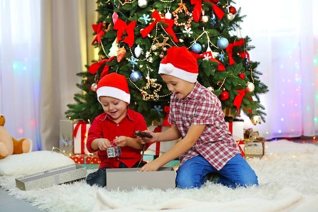 Zwei niedliche kleine brüder, die geschenke auf weihnachtsdekoration öffnen