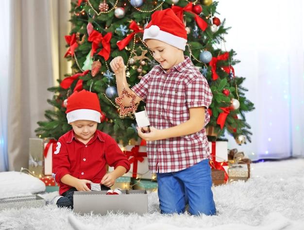 Zwei niedliche kleine brüder, die geschenke auf weihnachtsdekorationshintergrund öffnen