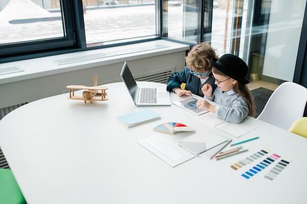 Zwei niedliche kleine designer, die online-daten im touchpad studieren, während sie über neues kreatives projekt durch schreibtisch arbeiten