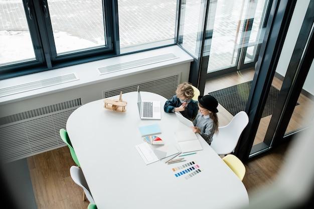 Zwei niedliche kleine designer, die über online-daten beraten, während sie neues kreatives projekt durch klassenzimmerfenster vorbereiten
