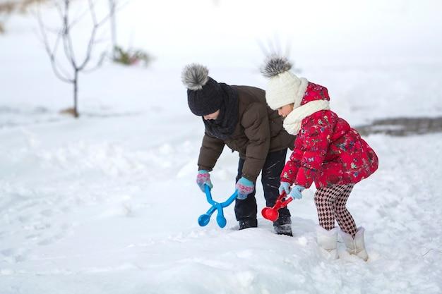 Zwei niedliche kleine kinder in warmer kleidung mit hellen schneeklammern, die spaß haben, schneebälle am kalten wintertag auf weißem hellem unscharfem kopierraumhintergrund zu machen. aktivitäten im freien, ferienspiele.