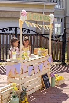 Zwei niedliche kleine mädchen, die hausgemachte limonade durch hölzernen stall am heißen sommertag auf hintergrund des zauns und des hauses dahinter verkaufen