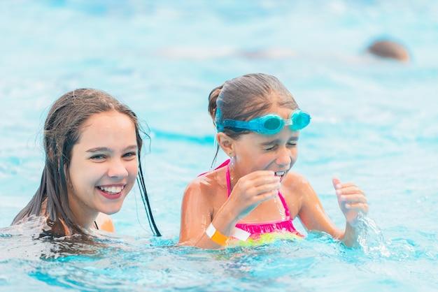 Zwei niedliche kleine schwestermädchen schwimmen im pool während des urlaubs an einem sonnigen warmen sommertag