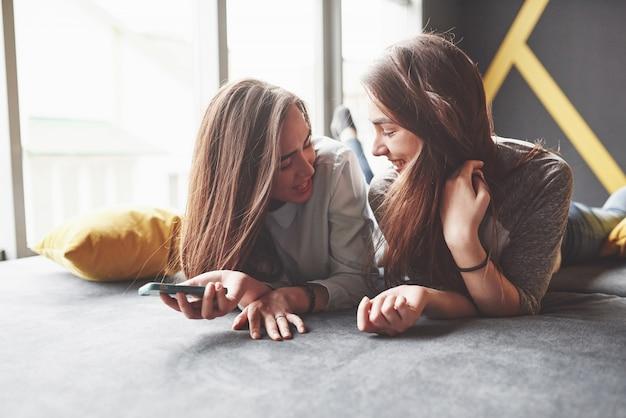 Zwei niedliche lächelnde zwillingsschwestern, die smartphone halten und selfie machen. mädchen liegen auf der couch posierend und freude