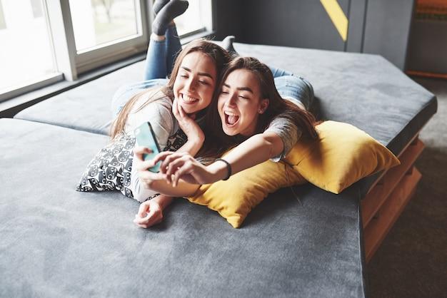 Zwei niedliche lächelnde zwillingsschwestern, die smartphone halten und selfie machen.