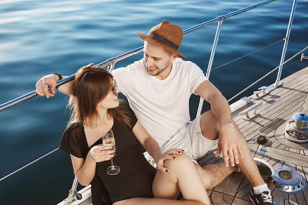 Zwei niedliche leute in der beziehung hängen auf der yacht, sitzen auf dem boden und sprechen, während sie mit freunden zur insel reisen. das verliebte paar reiste ins ausland, um sich sorglos zu fühlen und sich zu amüsieren