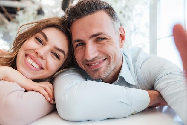Zwei niedliche leute mann und frau, die spaß zusammen haben und schönes selfie machen, während sie mittagspause im restaurant haben