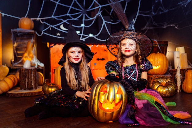 Zwei niedliche lustige schwestern feiern den feiertag. lustige kinder in den karnevalskostümen bereit zu halloween.