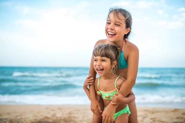 Zwei niedliche positive kleine mädchenschwestern hoben ihre hände hoch, während sie während der ferien an einem warmen sommertag auf see schwammen. konzept von gesunden und freudigen kindern