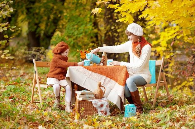 Zwei niedliche schwestern, die tee im herbstgarten trinken