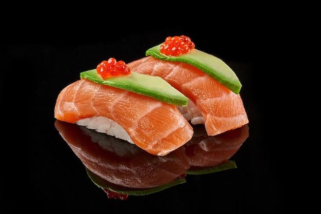 Zwei nigiri-sushi mit lachs-avocado-kaviar auf schwarzer oberfläche