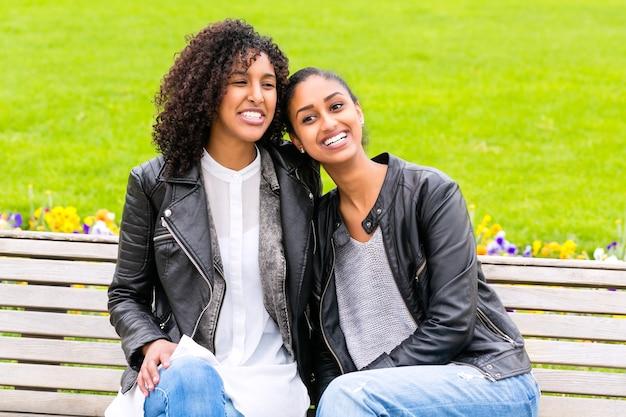 Zwei nordafrikanische jugendlich freunde, die zusammen auf parkbank sitzen und sprechen