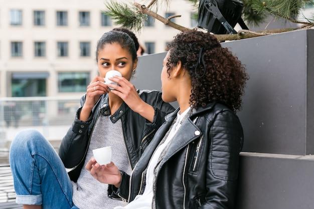 Zwei nordafrikanische jugendlich freunde, die zusammen kaffee draußen trinken
