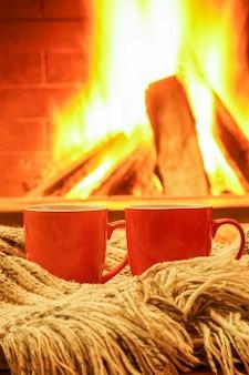 Zwei orange becher für tee oder kaffee, wollsachen gegen gemütlichen kaminhintergrund.