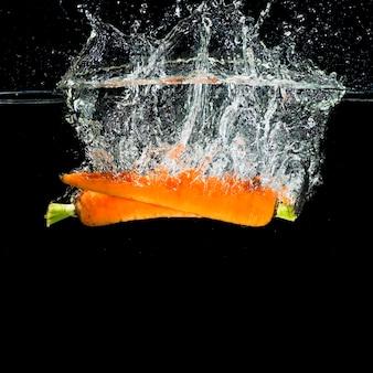 Zwei orange karotten, die in wasserspritzen fallen