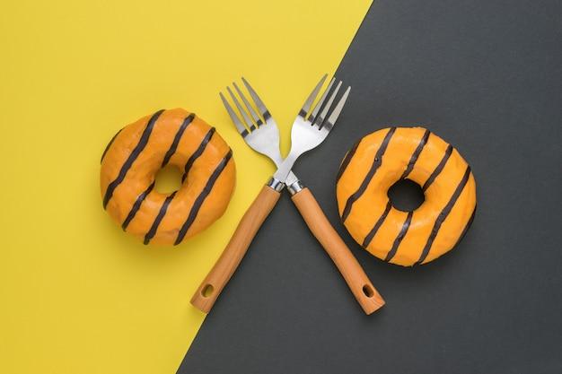 Zwei orangefarbene donuts und zwei gabeln auf gelbem und schwarzem hintergrund. ein beliebter süßer snack.