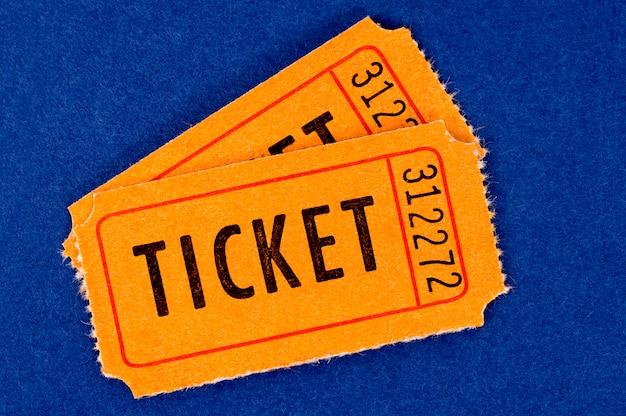 Zwei orangefarbene tickets auf blau.
