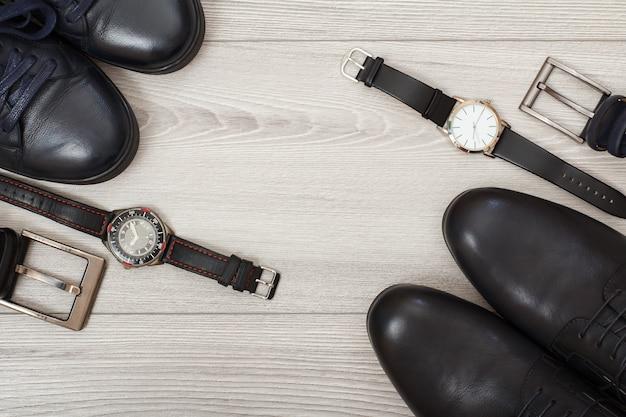 Zwei paar herrenschuhe aus schwarzem leder, zwei gürtel für männer und zwei armbanduhren auf grauem holzhintergrund. accessoires für herren. ansicht von oben