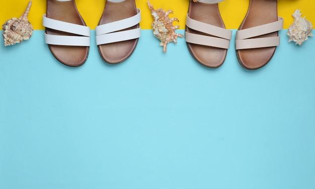 Zwei paar modische ledersandalen aus leder, muscheln auf farbiger pastelloberfläche, draufsicht, minimalismus, kopierraum