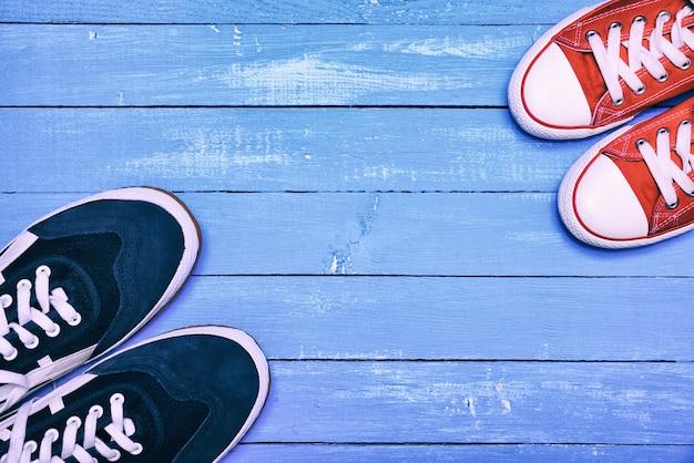 Zwei paar sportschuhe, blaue herrenschuhe und rote damenschuhe