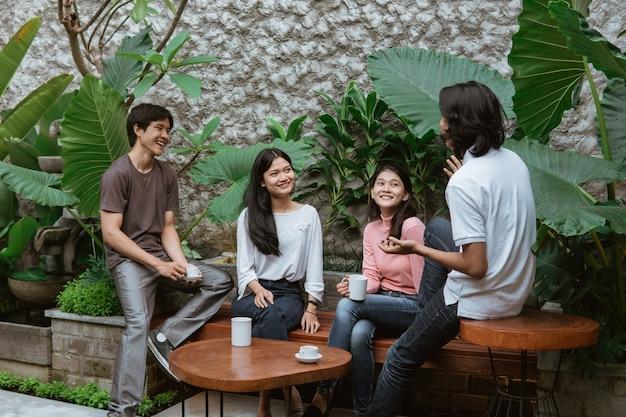 Zwei paar teenager, die beim sitzen auf tisch und holzbank im hausgarten plaudern