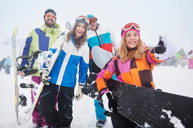 Zwei paare, die spaß haben und snowboarden