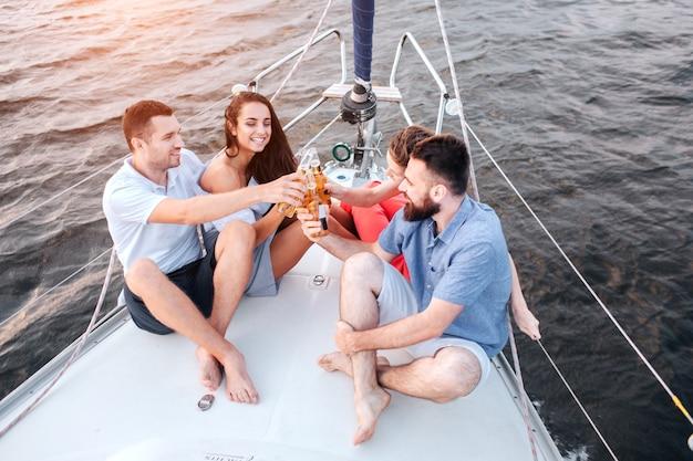 Zwei paare sitzen auf bug der yacht und jubeln mit bier
