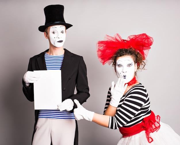 Zwei pantomimen mit einem schild für werbung, aprilscherz-konzept.