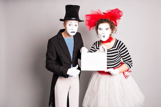 Zwei pantomimen mit einem werbeschild auf grauem hintergrund mit einem werbeschild