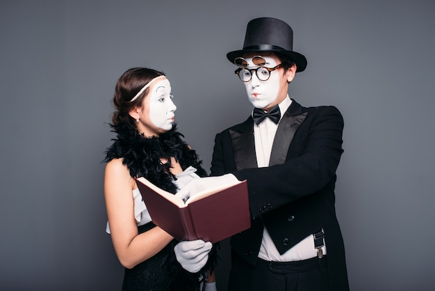 Zwei pantomimetheaterkünstler, die mit buch aufwerfen