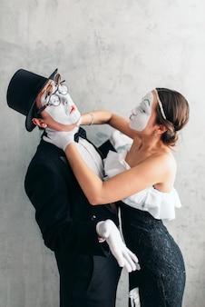 Zwei pantomimetheaterkünstler treten auf. pantomime schauspieler mit weißen make-up-masken auf gesichtern