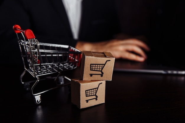 Zwei papierboxen in der nähe des einkaufswagens. online-shopping-, e-commerce- und lieferkonzept