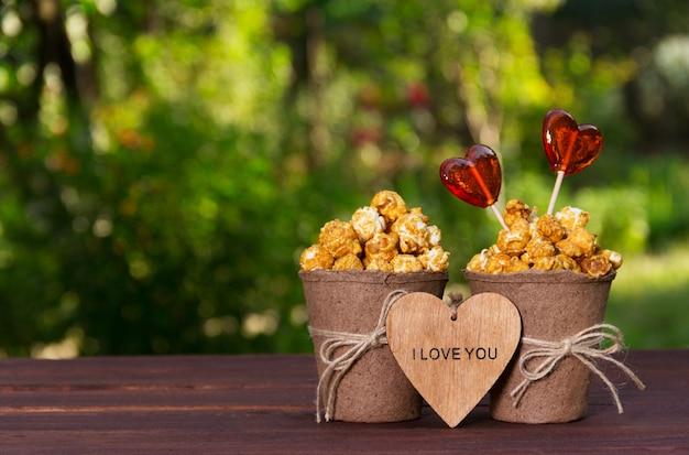 Zwei papiereimer mit popcorn und herzförmigen lutschern