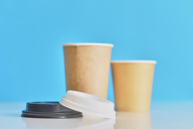 Zwei papierkaffeetassen auf blau. kaffee für liebespaar