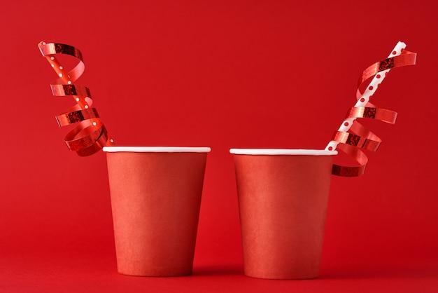 Zwei papierkaffeetassen mit dekorationen und stroh auf rotem backgrond. valentinstag festliches konzept