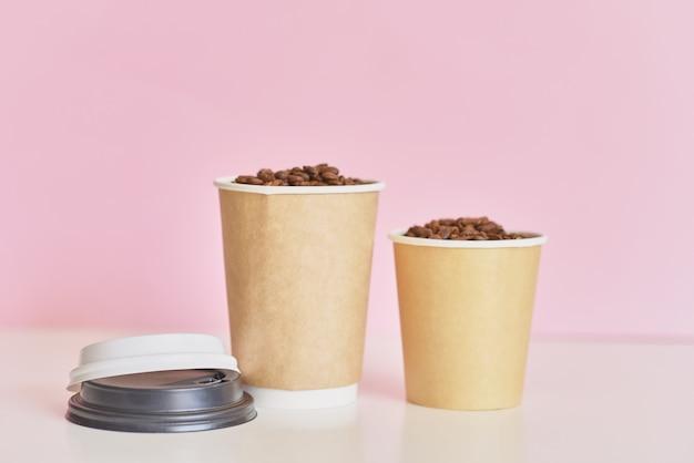 Zwei papierkaffeetassen mit kaffeebohnen auf rosa