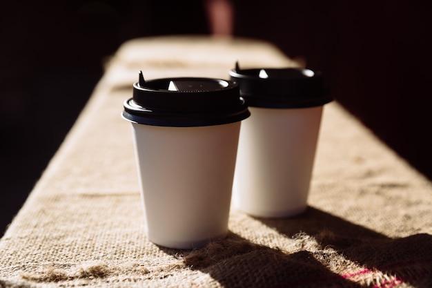 Zwei papierkaffeetassen zerstoßen auf eine tasse kaffeebohnen zum mitnehmen aus sackleinen