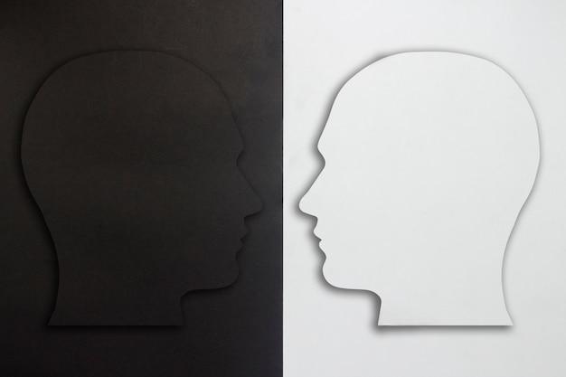 Zwei papierköpfe, schwarz und weiß auf einem schwarzen und weißen hintergrund. das konzept einer gespaltenen persönlichkeit, unterschiedlicher meinungen, streit, krieg. flache lage, draufsicht.