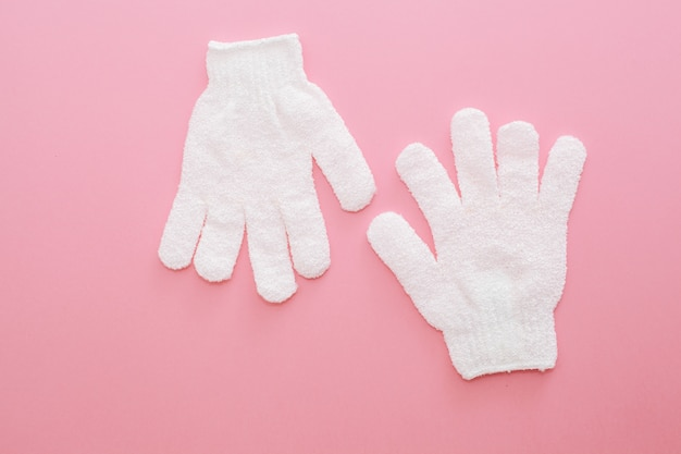Zwei peeling-massage-handschuh für die dusche auf rosa hintergrund. handschuhe für den einsatz in der dusche für massage und peeling.