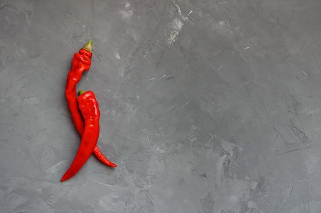 Zwei peperoni-paprikas oder paprikas auf einem grauen hintergrund. würziges essen, ansicht von oben.