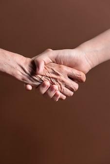 Zwei personen aus unterschiedlicher generation schütteln sich in einer vereinbarung die hand