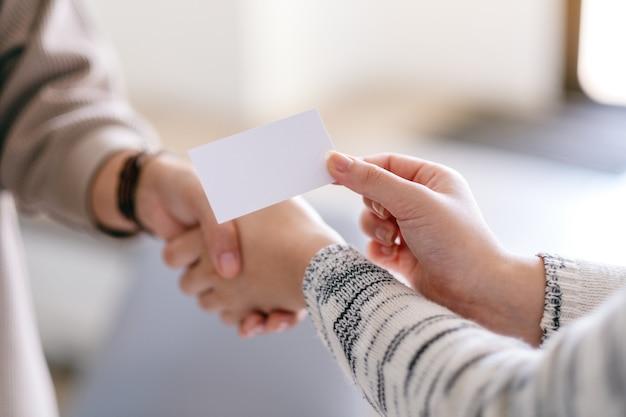 Zwei personen, die hände schütteln und leere visitenkarten austauschen