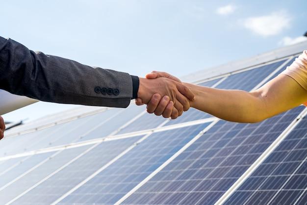 Zwei personen, die nach abschluss des abkommens im bereich erneuerbare energien ein händeschütteln gegen solarpanel haben